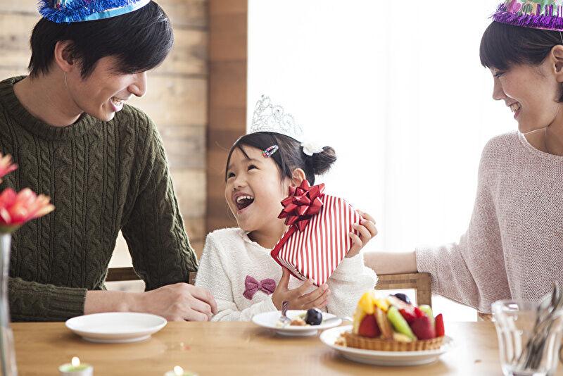 家族で笑いながら誕生日を過ごす画像です