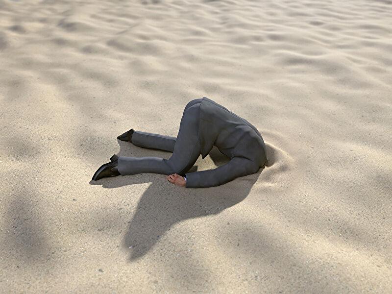 砂の中に頭を突っ込んでいるサラリーマンの画像